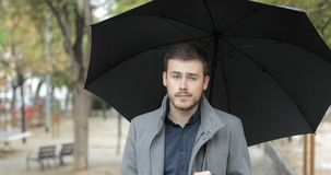 Angry man complaining in a rainy day looking at you. Front view portrait of an angry man complaining holding an umbrella in a rainy day looking at you in winter stock video