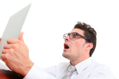 Angry man with computer. Angry man using computer on white background Royalty Free Stock Image
