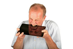 Angry man consuming his tablet computer Royalty Free Stock Photography