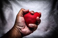 Angry man crushing red heart in hand., unrequited love., love co Royalty Free Stock Image