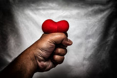 Angry man crushing red heart in hand., unrequited love., love co Stock Image
