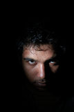Angry man in darkness. Angry young man in the darkness Royalty Free Stock Photography