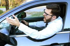 Angry man driving a car. And raising his hand violently stock photos