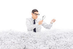 Angry man examining a pile of shredded paper Stock Photos