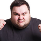 Angry man fighting with clenched fists, isolated. Feeling furious. Fighting fat man holding fists clenched, expressing anger, white isolated studio background Royalty Free Stock Image