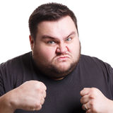 Angry man fighting with clenched fists, isolated. Furious angry fat man holding fists clenched, expressing anger, white isolated studio background Royalty Free Stock Photography