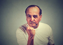Angry man with fist up  on gray wall background Stock Photos