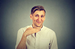 Angry man gesturing with hand to stop talking cut it out. Angry young man gesturing with hand to stop talking, cut it out isolated on gray background. Negative Stock Photo