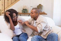 Angry man grabbing his scared partner on sofa Stock Photos