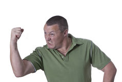 Angry man in green shirt. Male showing anger in a green shirt, isolated background Stock Images