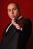 Angry man with gun. Angry looking man pointing a gun at the camera. Red background to symbolize danger Stock Image