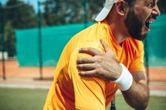 Angry man having pain in shoulder. Side view bearded grumpy male athlete holding hand while having trauma there during game on modern court royalty free stock photos