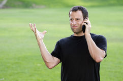 Angry man on his cell phone. Frustrated angry man on his cell phone outdoors in a black t-shirt Stock Images