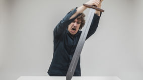Angry man hitting his desk with a sword Royalty Free Stock Photography