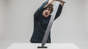 Angry man hitting his phone with a sword Royalty Free Stock Photos