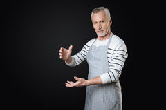 Angry man holding fictitious bottle. I have it. Delighted bearded gray-haired man wearing striped apron looking straight at camera standing over black background Stock Photos