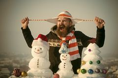 Angry man holding hat strings in hands. Holidays celebration concept. Hipster shouting on winter day. Christmas and new year. Snowmen and snow xmas tree on stock photo