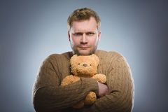 Angry man is holding a teddy bear and smiling on gray background Royalty Free Stock Images