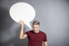 Angry man holding white empty speech ballon. Royalty Free Stock Image
