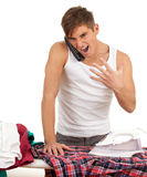 Angry man ironing clothes, housework Stock Photo