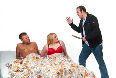 Angry man with knife finds his wife in bed with another man Stock Image