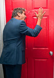 Angry man knocking on red door. Very upset businesman knocking on a door trying to collect a debt Stock Image