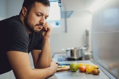 Angry man leaning on a kitchen countertop. And thinking Stock Photos