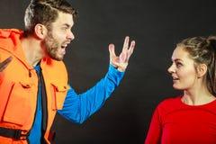 Angry man lifeguard shouting at woman lifesaver. Royalty Free Stock Image