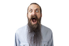 Angry man with long beard shouting. Isolated portrait of angry mad young man with long beard shouting. Concept of fundamentalism and anger management. Mock up Stock Images