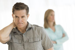 Angry Man Looking Away With Woman In Background At Home Stock Images