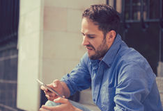 Angry man looking at mobile phone sitting on steps outside apartment complex Royalty Free Stock Photos