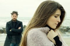 Angry man looking sad girlfriend after fight in front of the ocean stock photos