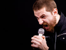 Angry man and loud scream at microphone stock image