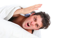 Angry man lying in bed Royalty Free Stock Images