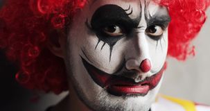 Portrait of sad and evil smiling scary clown on Halloween looking at camera. Angry man with makeup and red curly wig expressive horror emotions. Jester with stock video footage