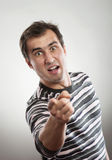 Angry man. Pointing at camera, studio shot, gray background Royalty Free Stock Photography
