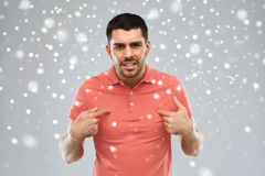 Angry man pointing finger to himself over snow Royalty Free Stock Photography
