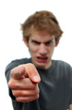 Angry man pointing the finger at you. Angry young man pointing his finger with rage at the camera. The hand is selectively in focus and there is white isolated Stock Photo