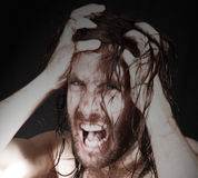 Angry man pulling hair. Portrait of bare chested madman pulling long wet hair, black background Royalty Free Stock Photos