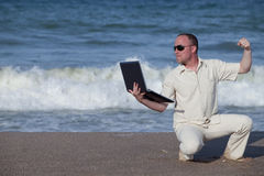 Angry man punching laptop at the beach. Sunburnt businessman at the beach punching his laptop Royalty Free Stock Photography