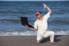 Angry man punching laptop at the beach. Frustrated sunburnt businessman at the beach with his laptop Stock Images