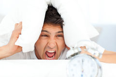 Angry man putting his head under the pillow Stock Photos