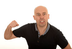 Angry man with raised fist. Portrait of angry bald man with raised fist clenching teeth, white background Royalty Free Stock Image