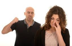 Angry man raising his fist. An angry man raising his fist at a woman Stock Image