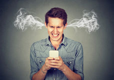 Angry man reading a text message on smartphone blowing steam coming out of ears. Frustrated angry man reading a text message on his smartphone blowing steam Stock Photo