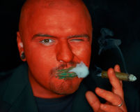 Angry man with red face smoking cigar. Royalty Free Stock Photography
