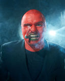 Angry man with red face smoking cigar. Royalty Free Stock Photos