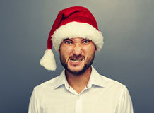 Angry man in santa hat over grey Stock Photo