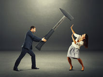 Angry man and scared woman. Angry screaming men holding big hammer and hitting scared woman. photo in the dark room Stock Image