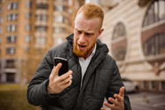 Angry man screaming on phone. Angry ginger man screaming on phone outdoor Royalty Free Stock Images